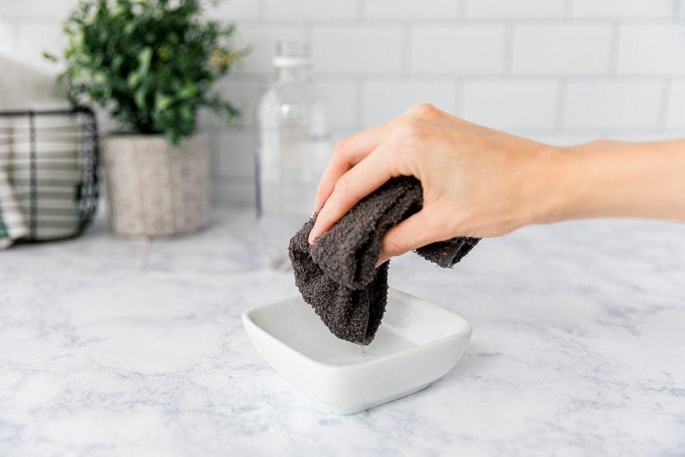 dipping a cloth into vinegar