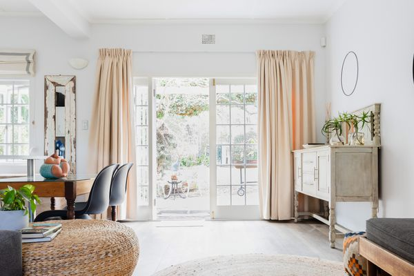 White French doors lined with tan curtains on each side in end of decorated room