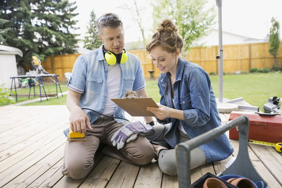Couple with clipboard preparing to sand backyard deck