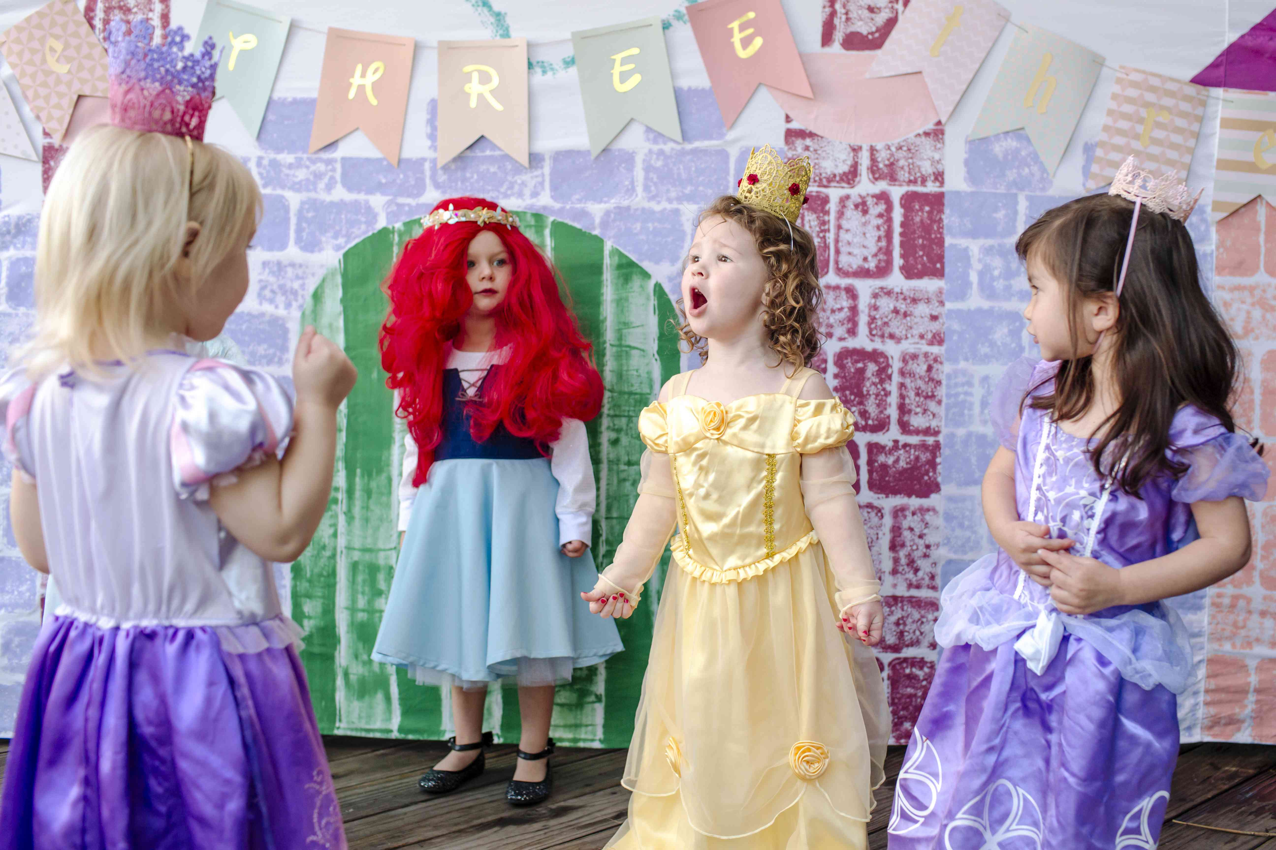 Playful girls against castle painting during princess party
