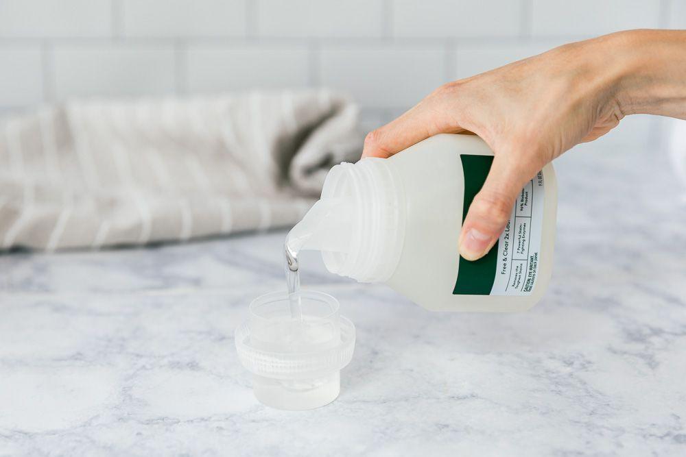 pouring detergent into a bottle cap