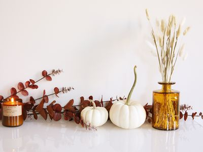 white pumpkins, a candle, and dried fall branches