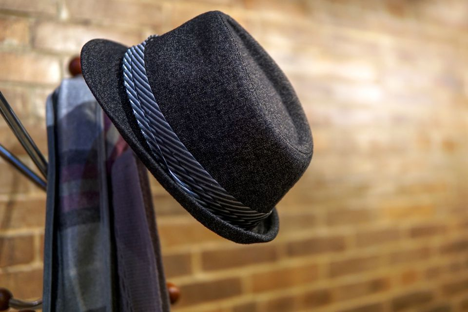 Hat And Scarf Hanging On Stand By Brick Wall
