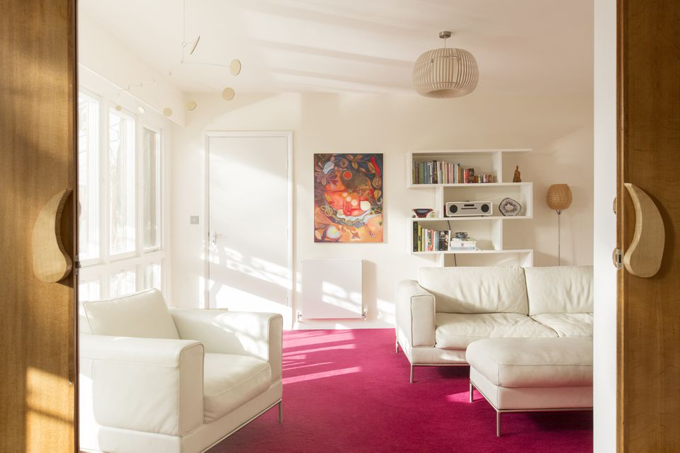 White leather couches on hot pink rug