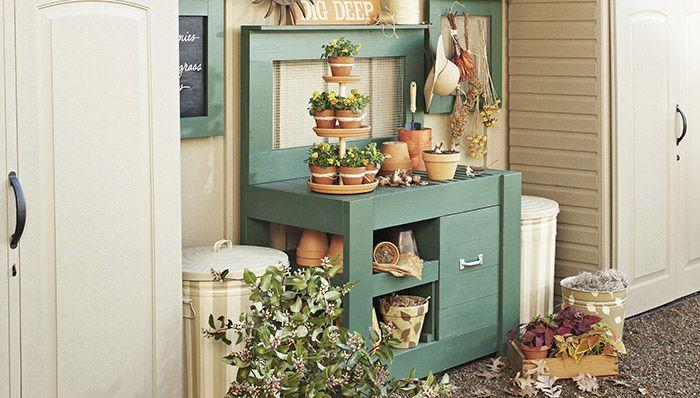 Un banco para macetas verde junto a un cobertizo