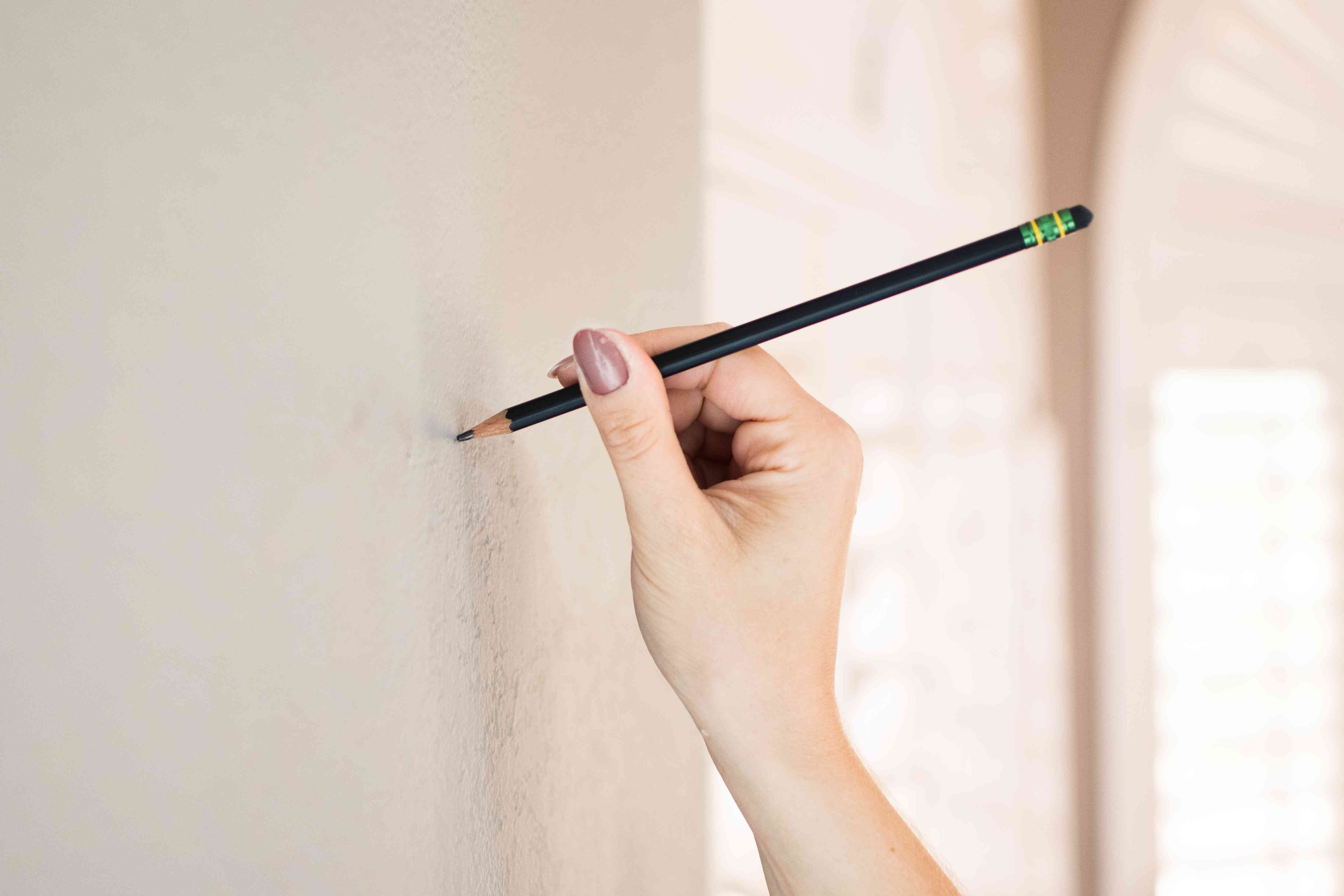 Pencil marking placement on wall for picture hanging