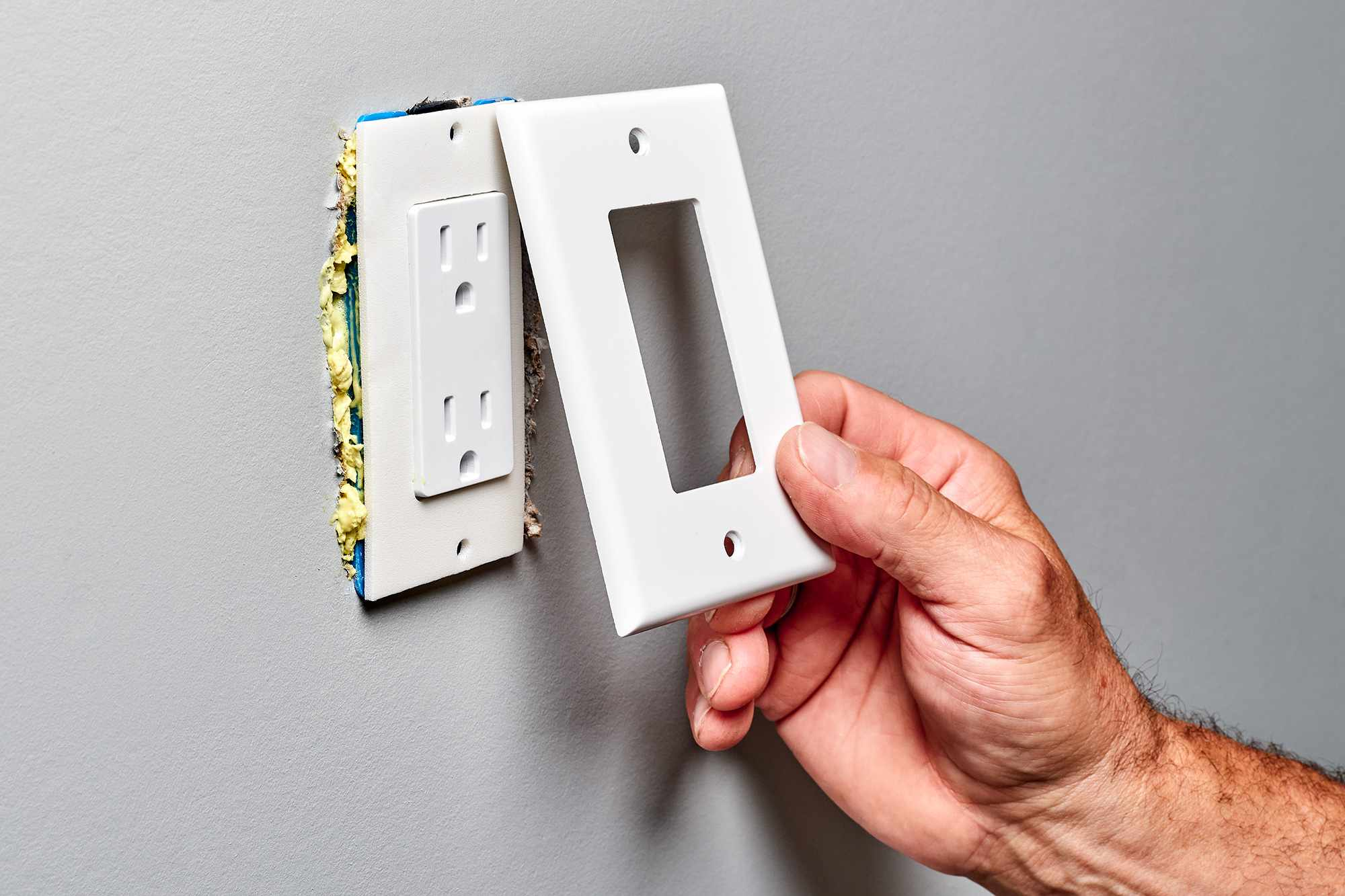 Neoprene insulating foam gaskets inserted behind reinstalled cover plate of electrical box