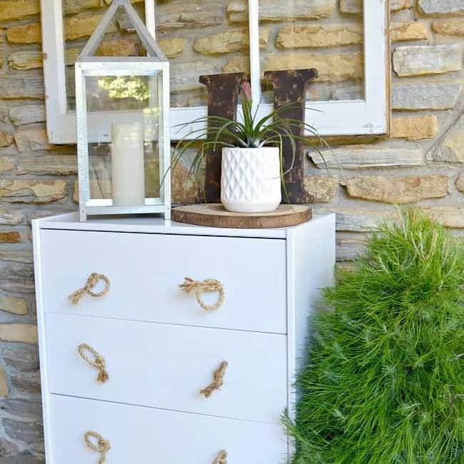 A white dresser outside on a porch