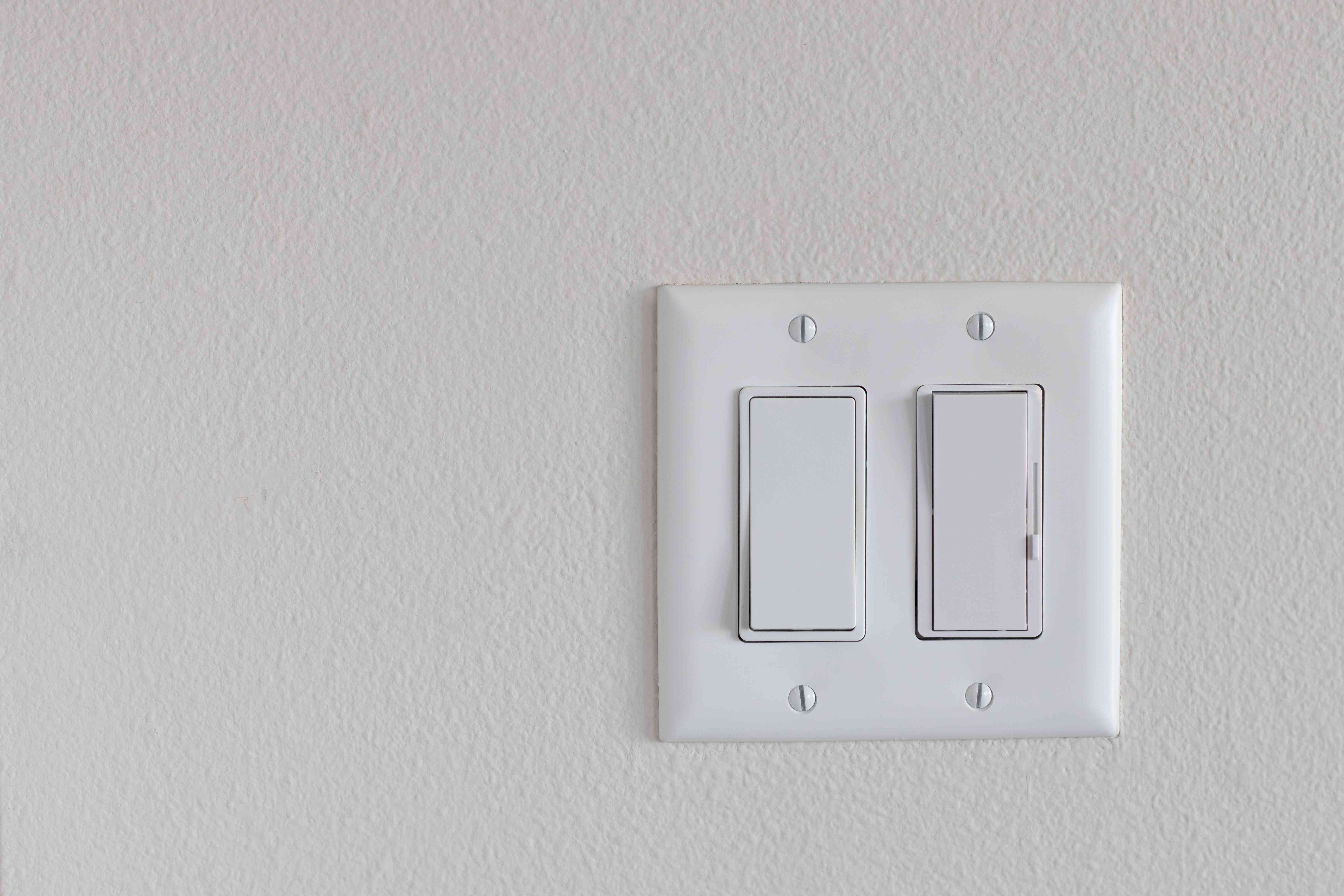 Light switch next to dimmer switch on white wall to lower electric bill