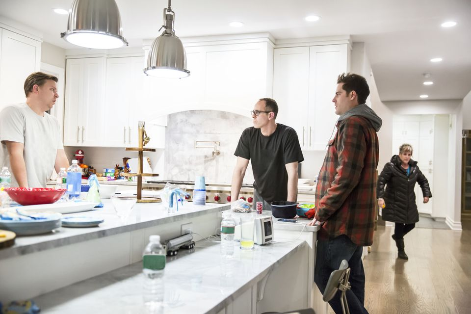 Three men hanging out together in the kitchen