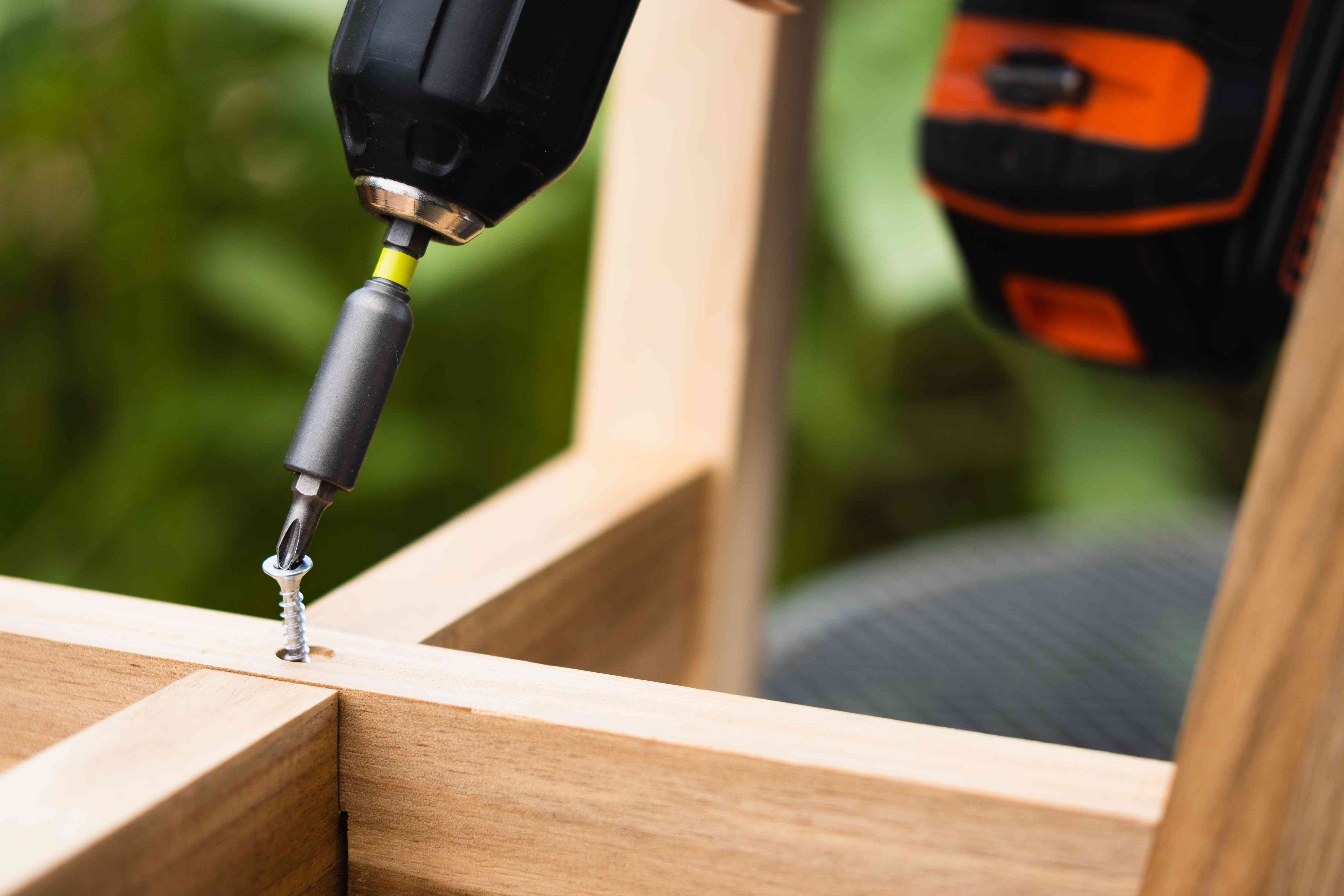 Larger bit drive attached to electric drill to remove stripped screw from wooden fixture