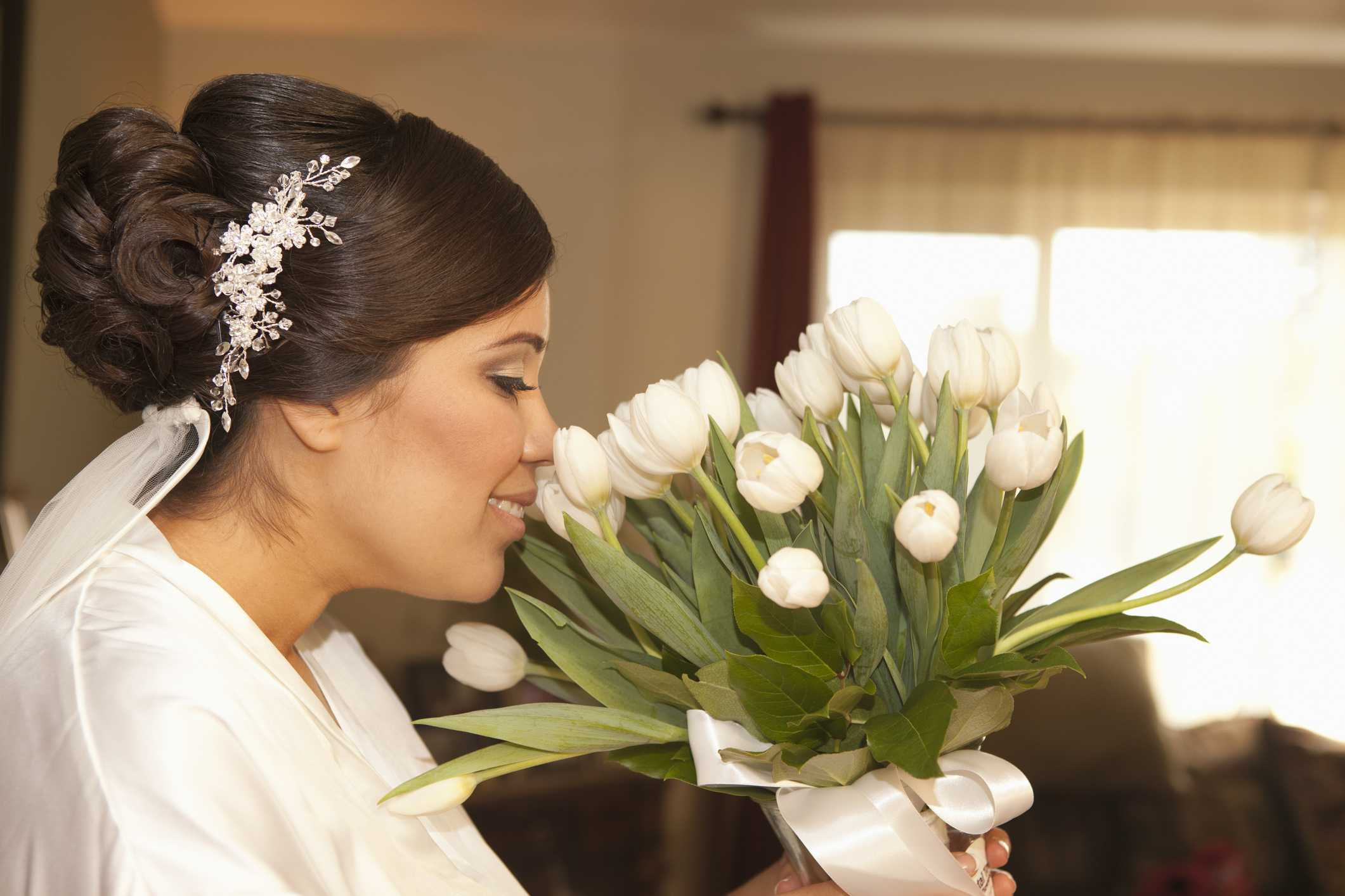Bride sniffing white tulip bouquet