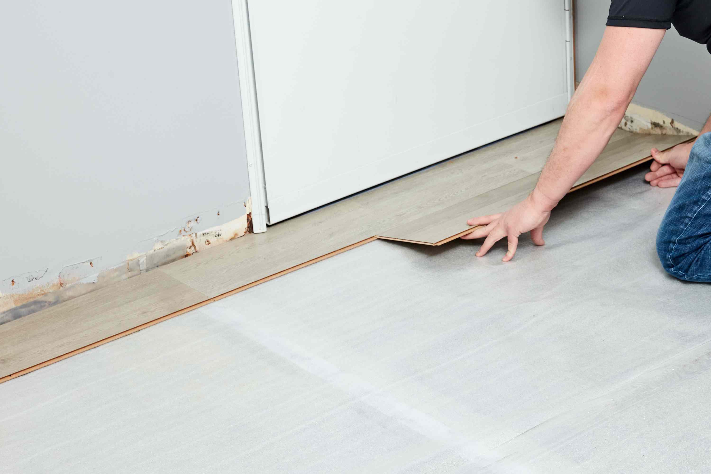 First row of laminate planks laid on floor