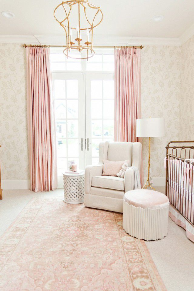 Pink and gold nursery with faded floral wallpaper and accents