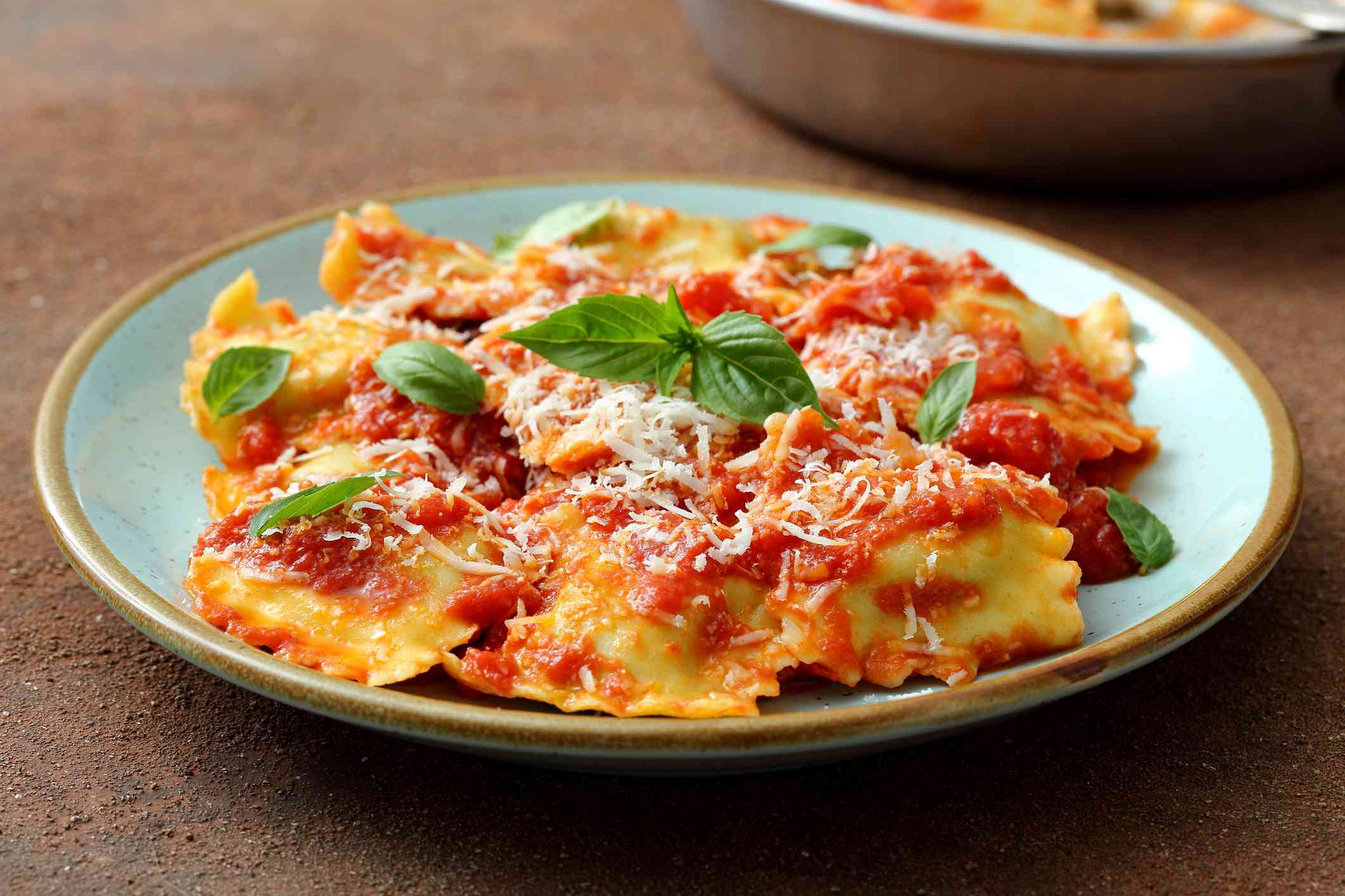 Ravioli with tomato sauce and parmesan in metal bowl on tabletop