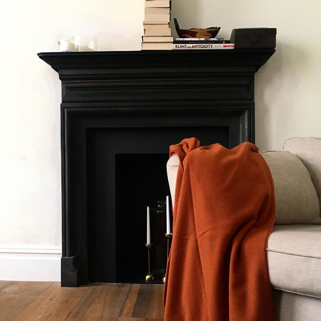 Living room with orange blanket and black fireplace