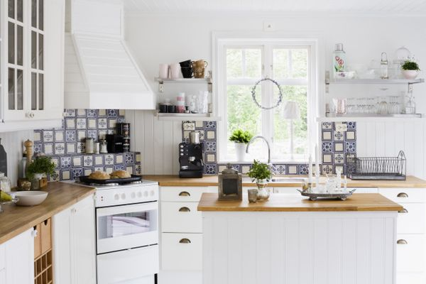 A white kitchen with light, natural wood and blue tile accents