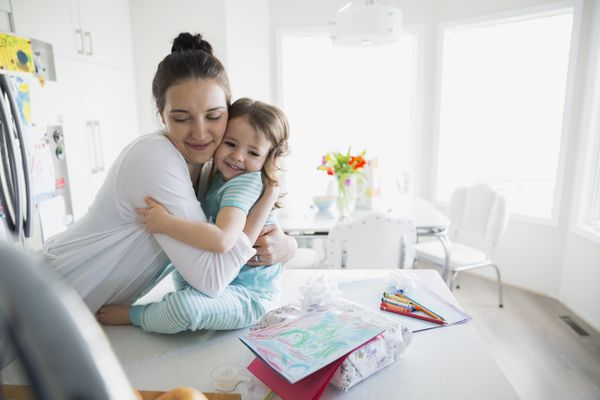 Affectionate mother and daughter in pajamas hugging