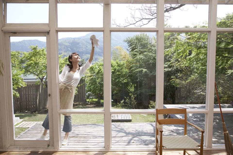 Woman on patio cleaning floor-to-ceiling windows