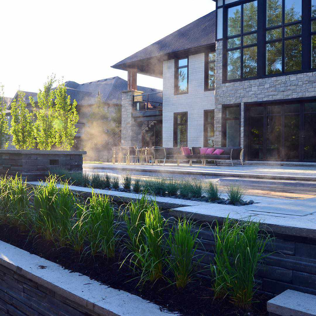 Ornamental grasses in retaining wall beds beside house and pool