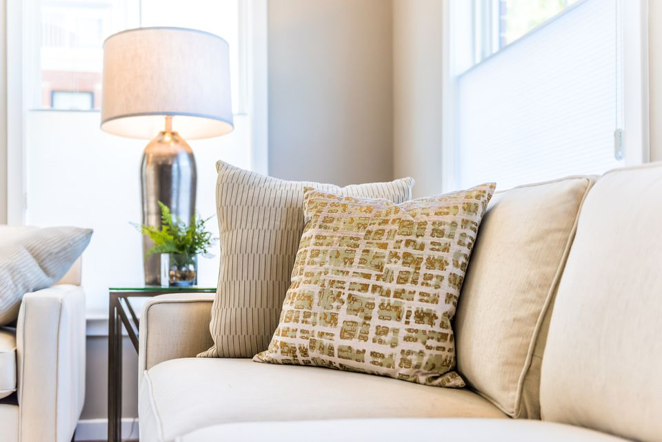 Closeup of two pillows on couch or sofa by bright window in modern apartment, house or home with staging of large beige, neutral white colors, lamp