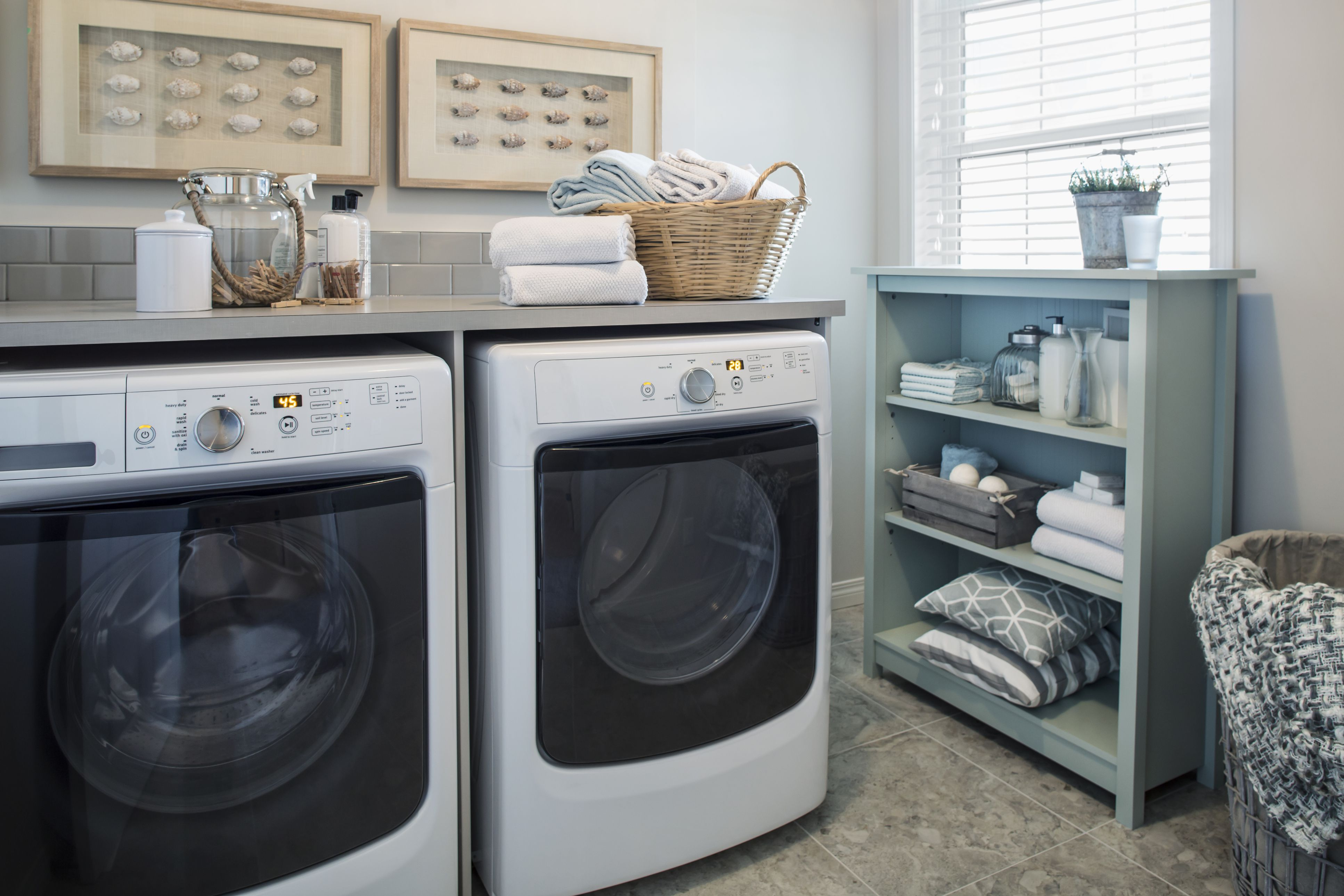 Washer and dryer with shelving in a laundry room.