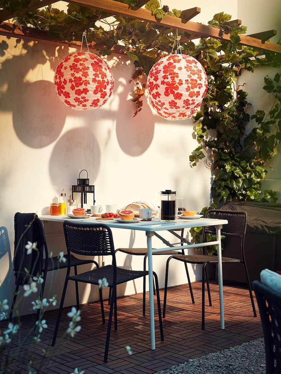 paper lanterns hanging from trellis over small table and chairs