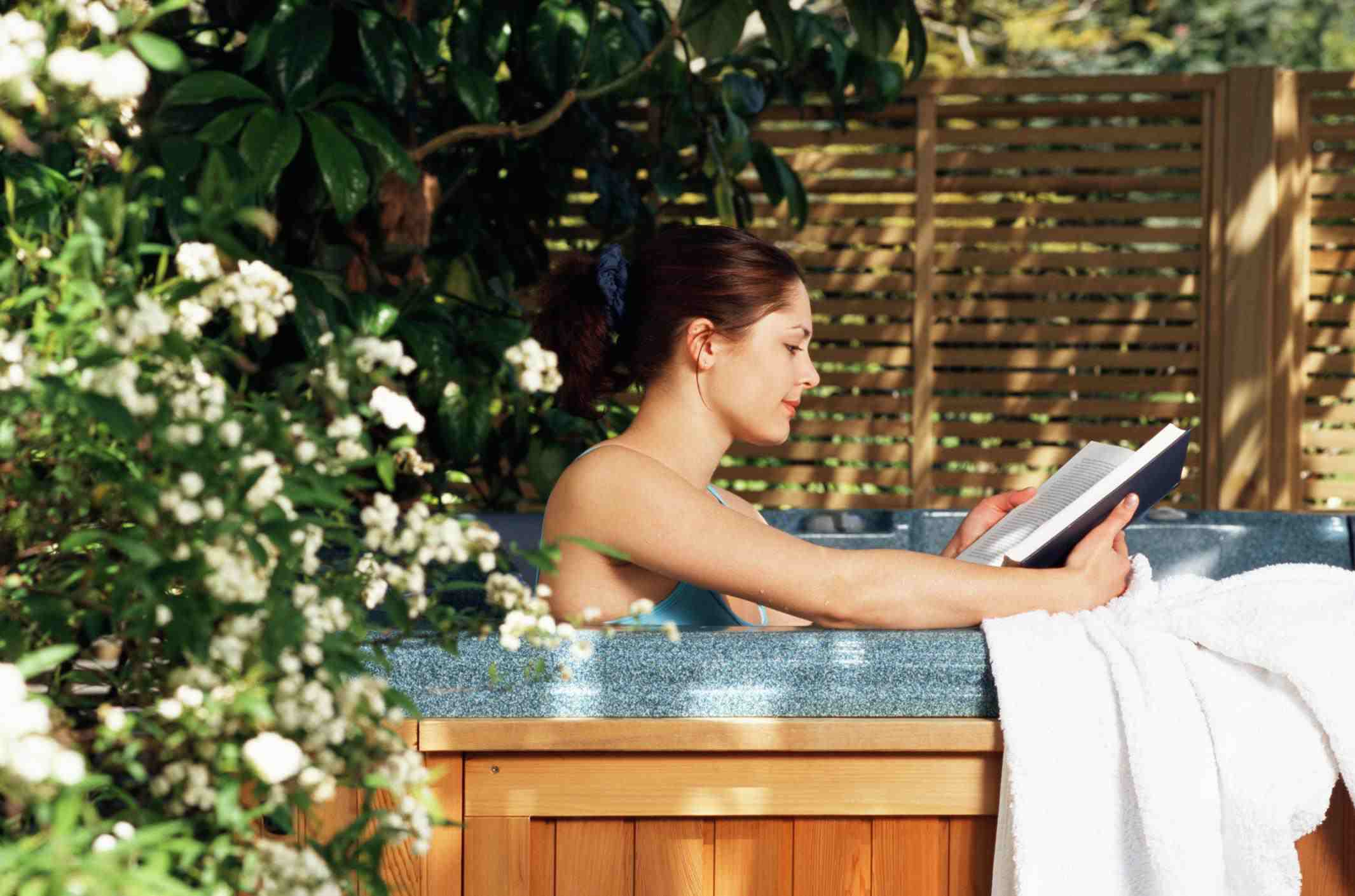 Woman reading in hot tub