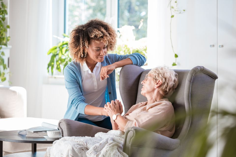 Caring nurse consoling an elderly lady