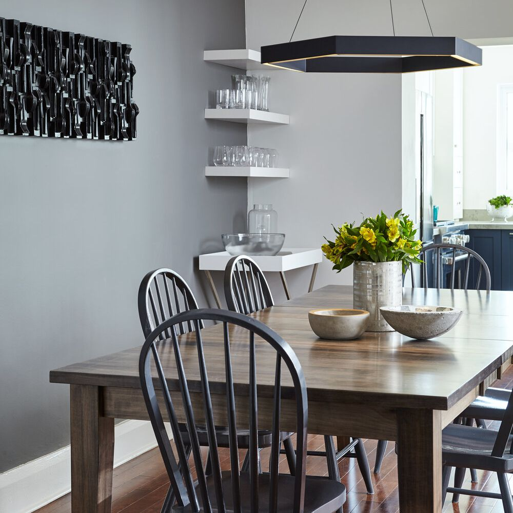 dining room with gray walls, wooden table, white floating shelves in corner