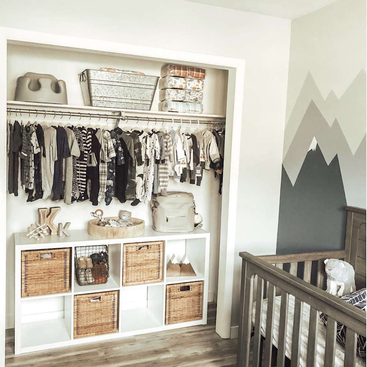 nursery with closet that has no doors, shelving storage on top and storage unit with wicker baskets below