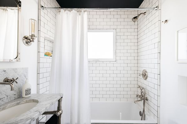 Small bathroom with white tile walls next to white marbled vanity and mirror