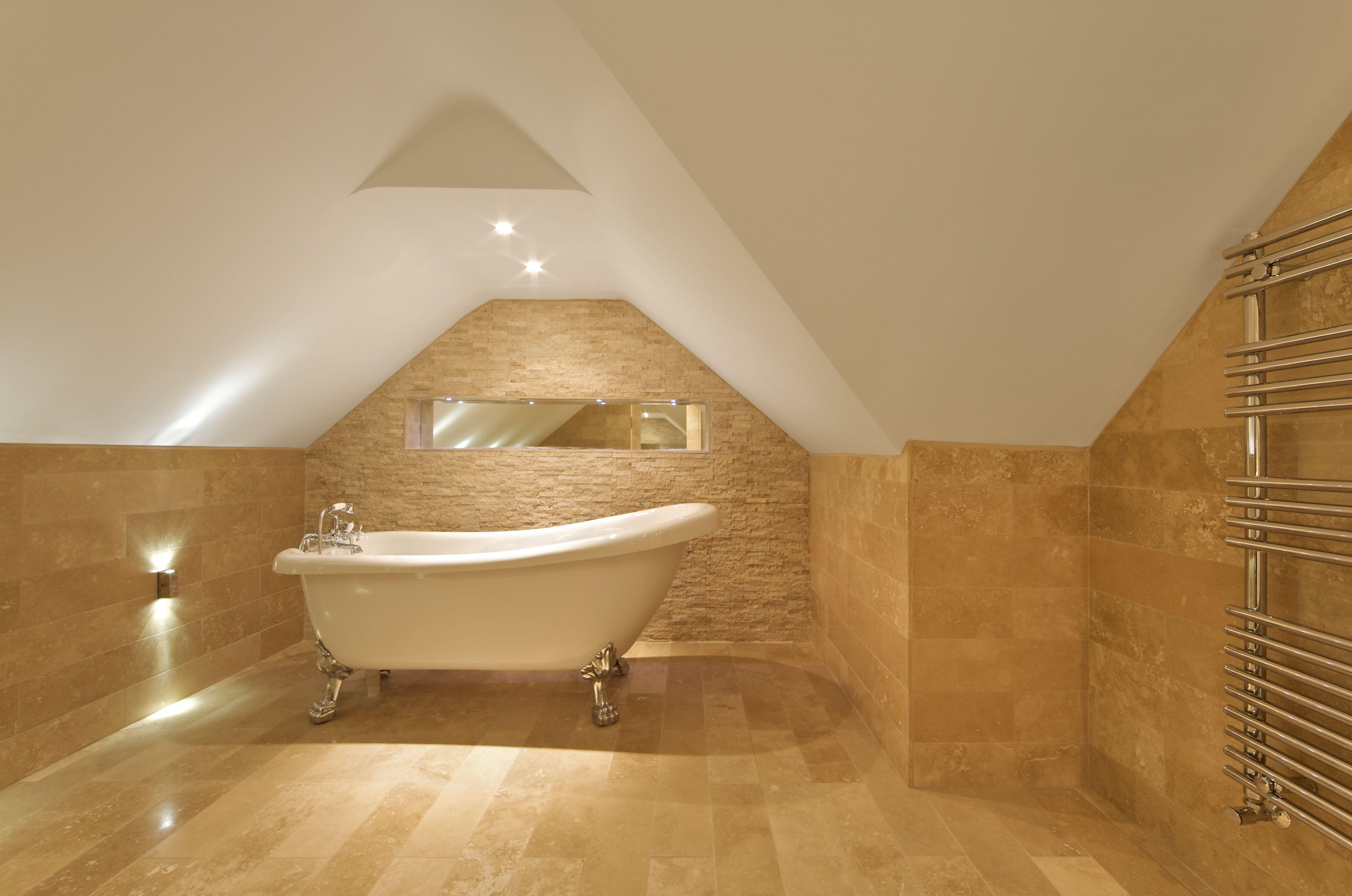 An elegant Roman bath tub in attic bathroom, marble tiles on floor and walls, modern towel rail