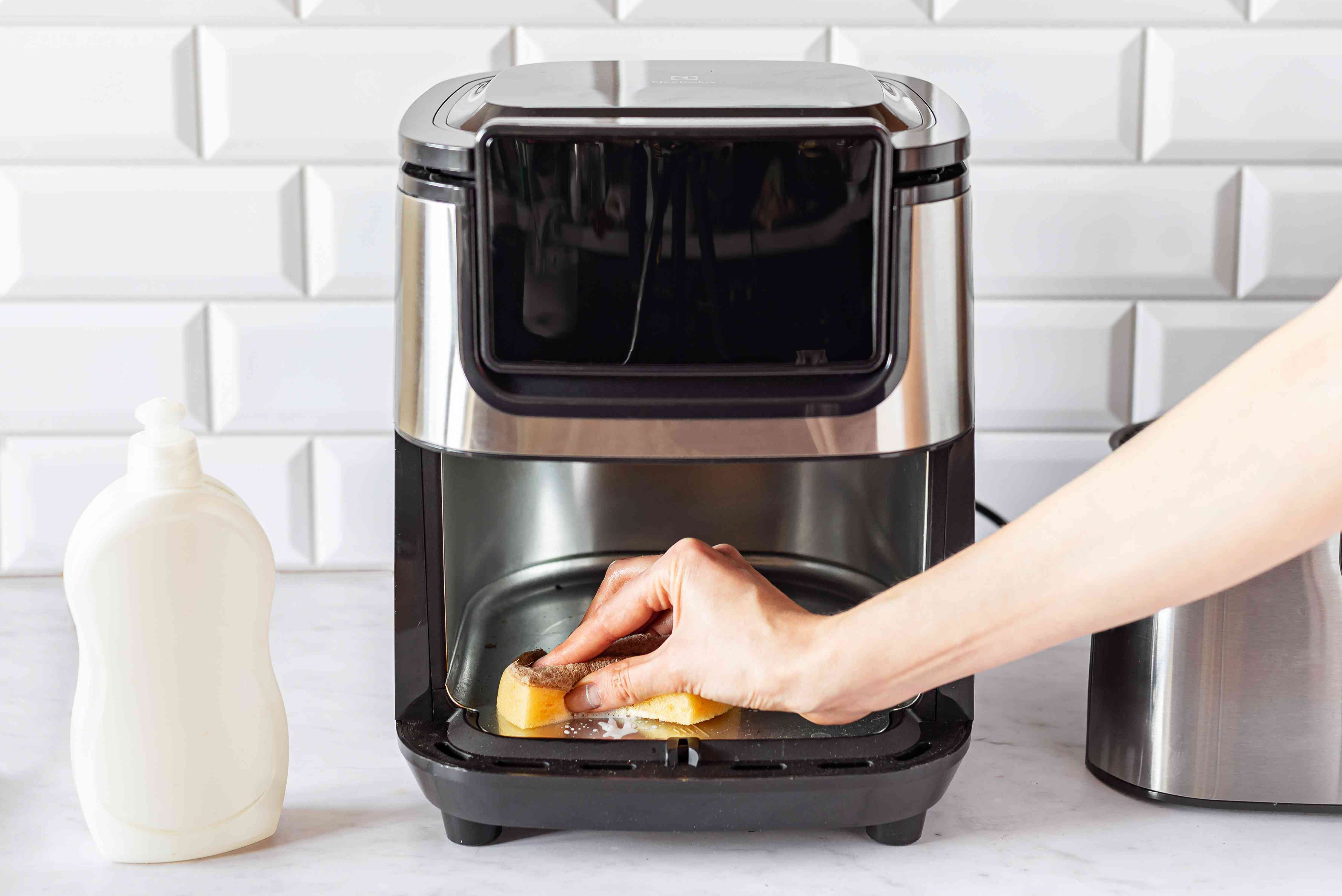 Air fryer base unit wiped down with non-abrasive sponge, warm water and dishwashing liquid