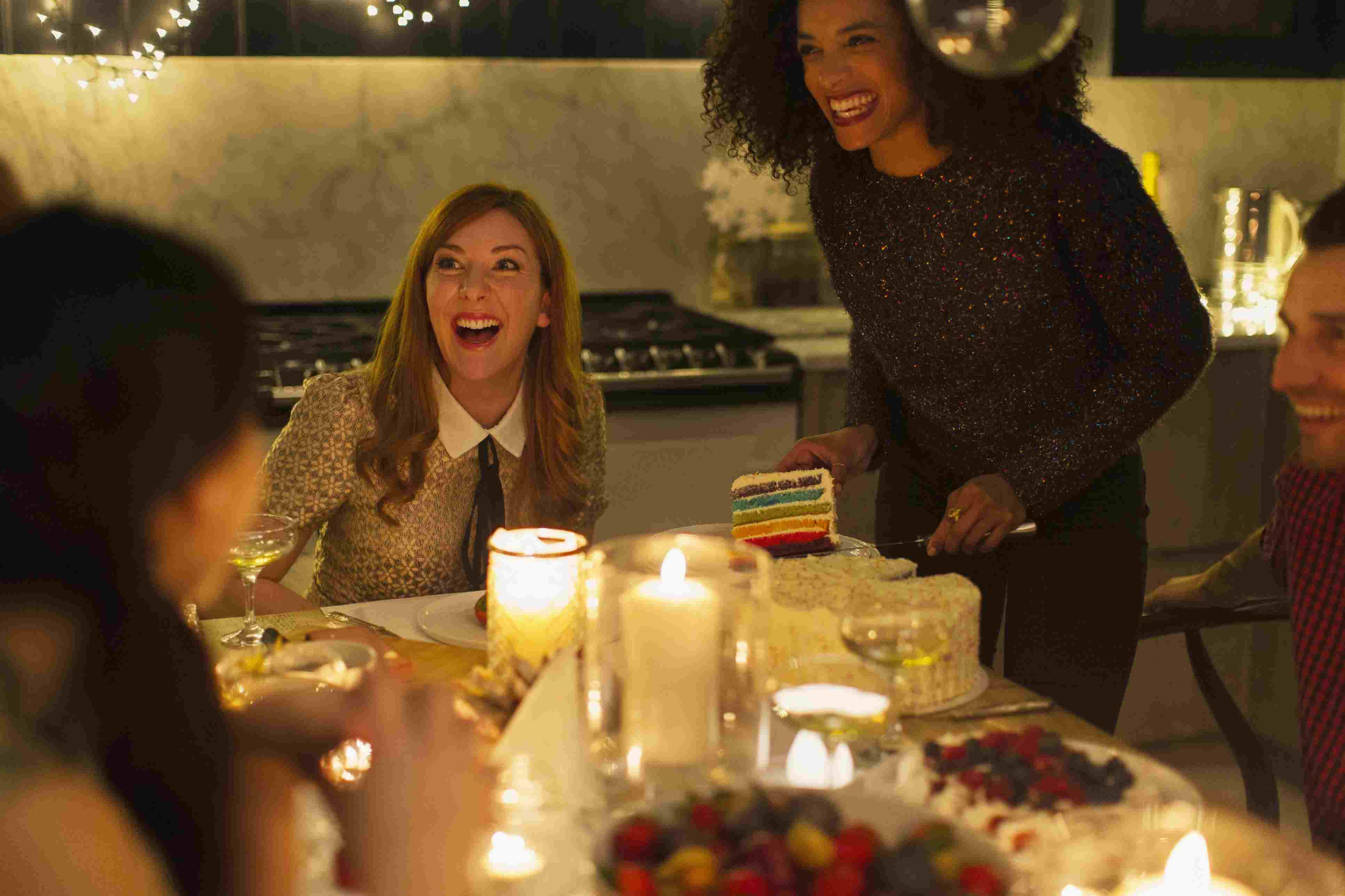 Laughing friends enjoying cake at candlelight dinner party