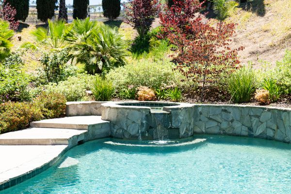 Swimming pool with rock-faced water feature surrounded by manicured landscape