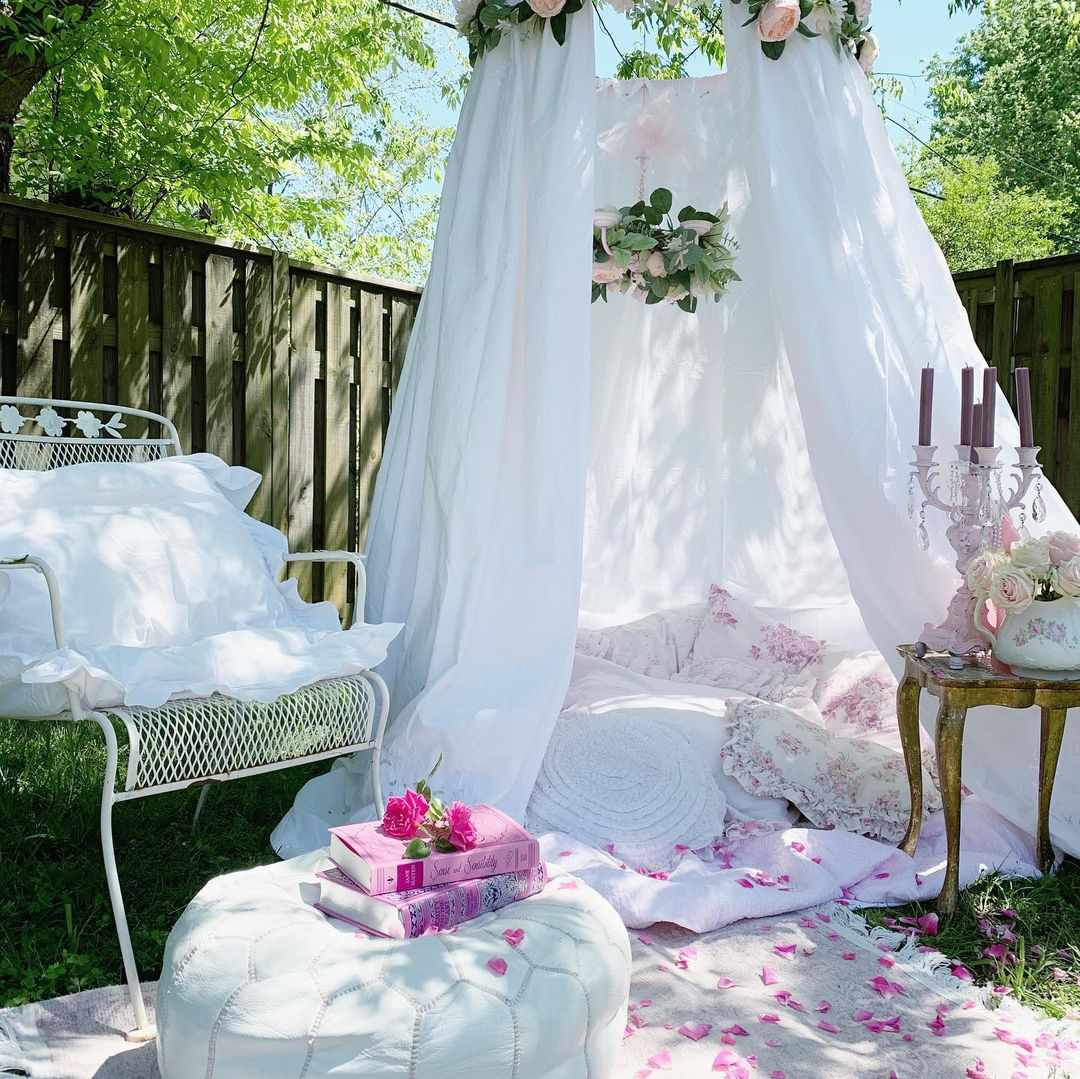 A DIY backyard tent made from white sheets and faux flowers.