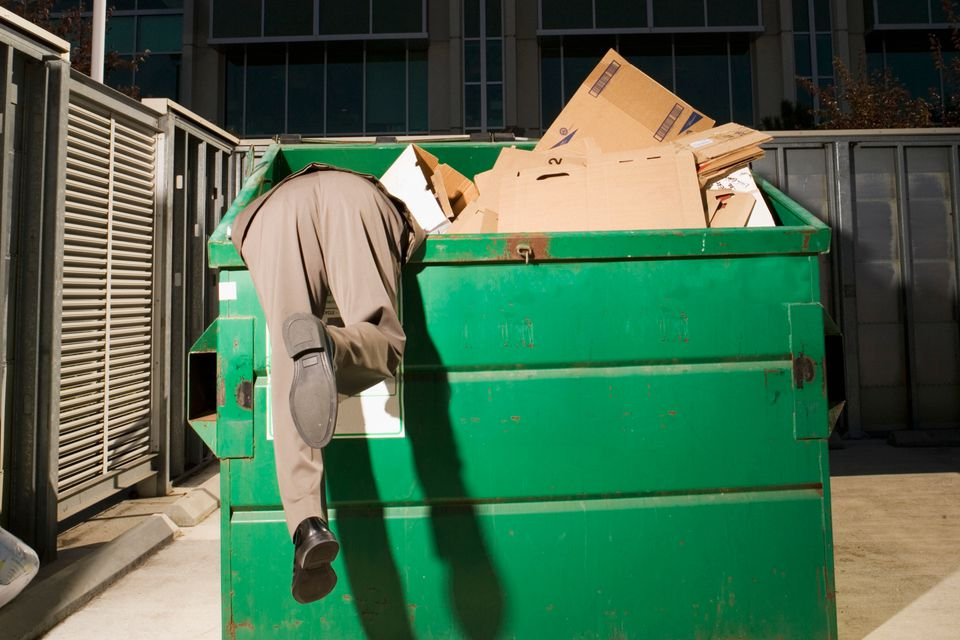 Man dumpster diving in green dumpster