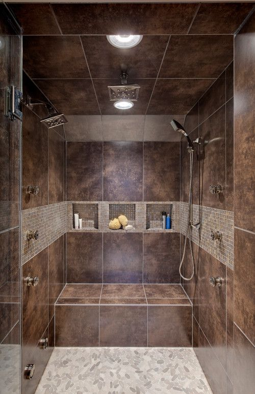 a double shower with dark brown tile