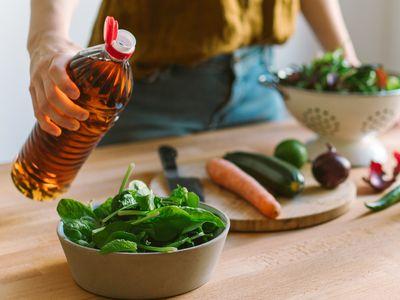 woman pouring vinegar onto lettuce