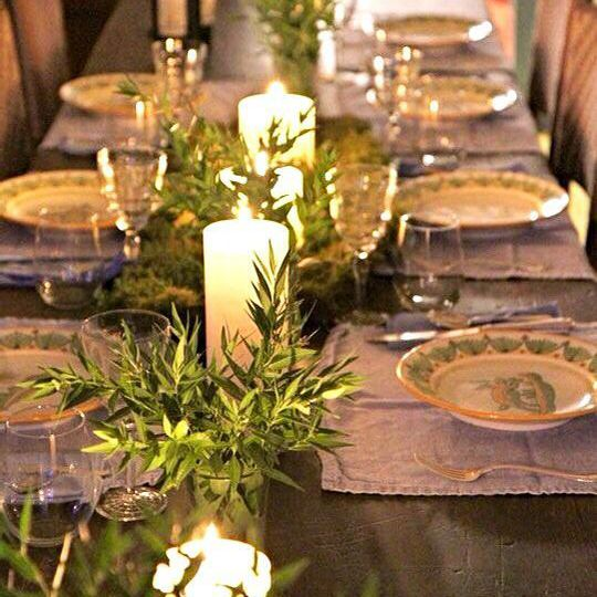 Table with lit candles, greenery, and place settings.