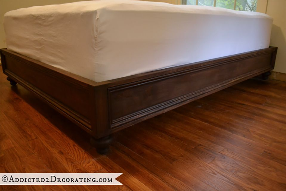 A close-up of a stained bed frame with a matress