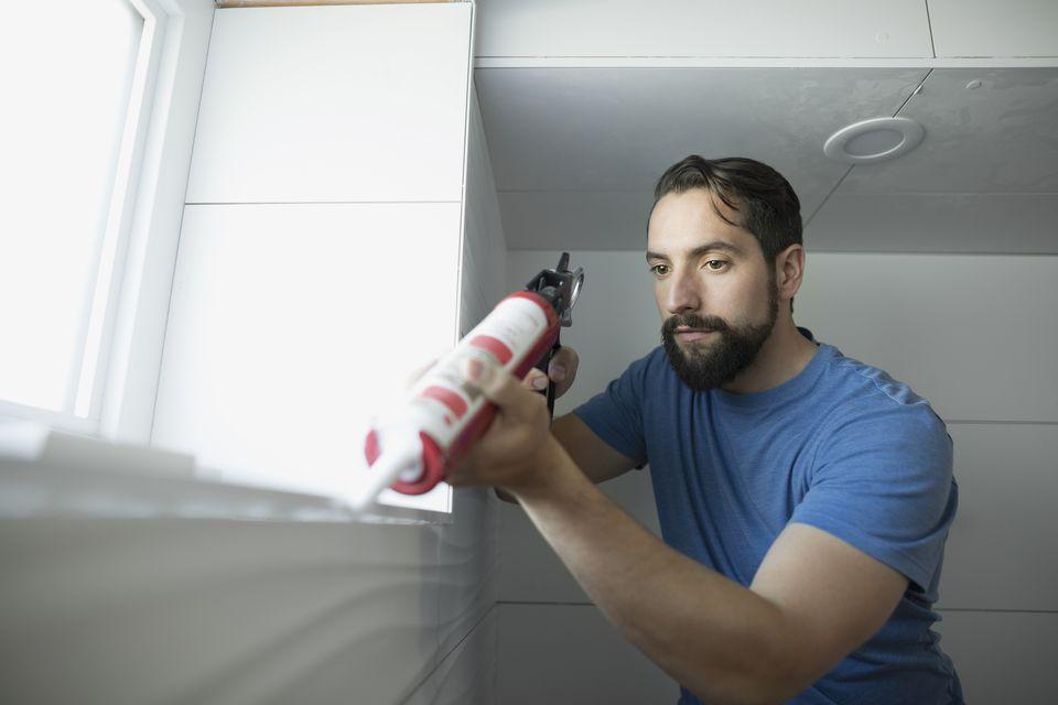 A man using a caulk gun on a windowsill