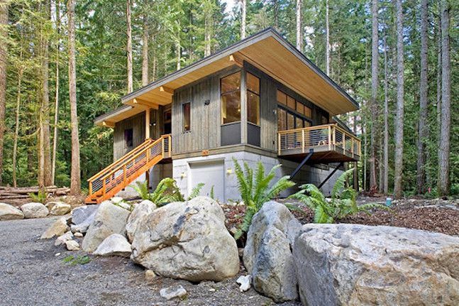 Large boulders in front of a modern house set into a woodland landscape.