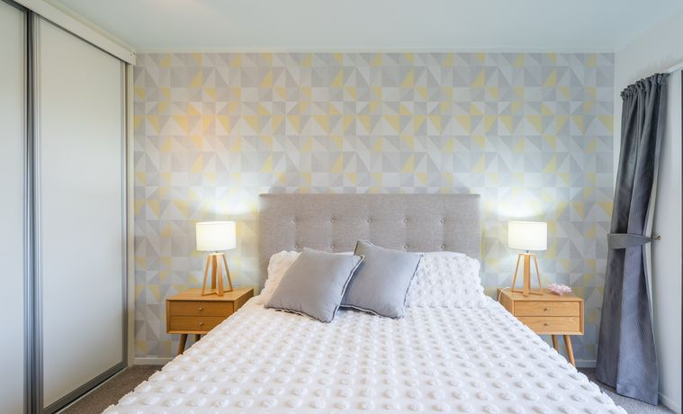 small bedroom, decorative pale yellow and gray triangle wallpaper on one wall, wooden bedside table on either side of bed