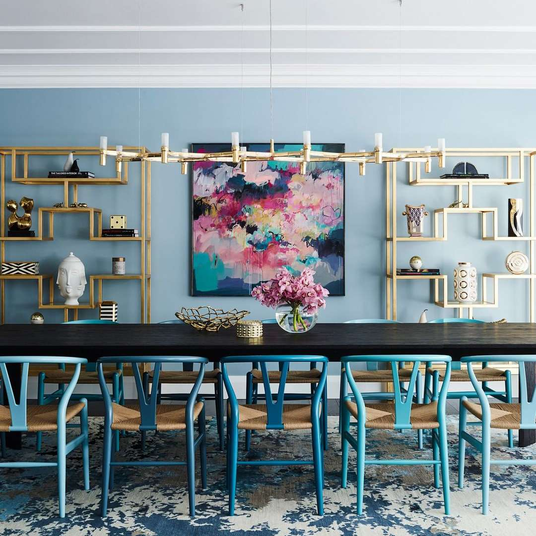 Dining table with blue chairs and a gold bookcase