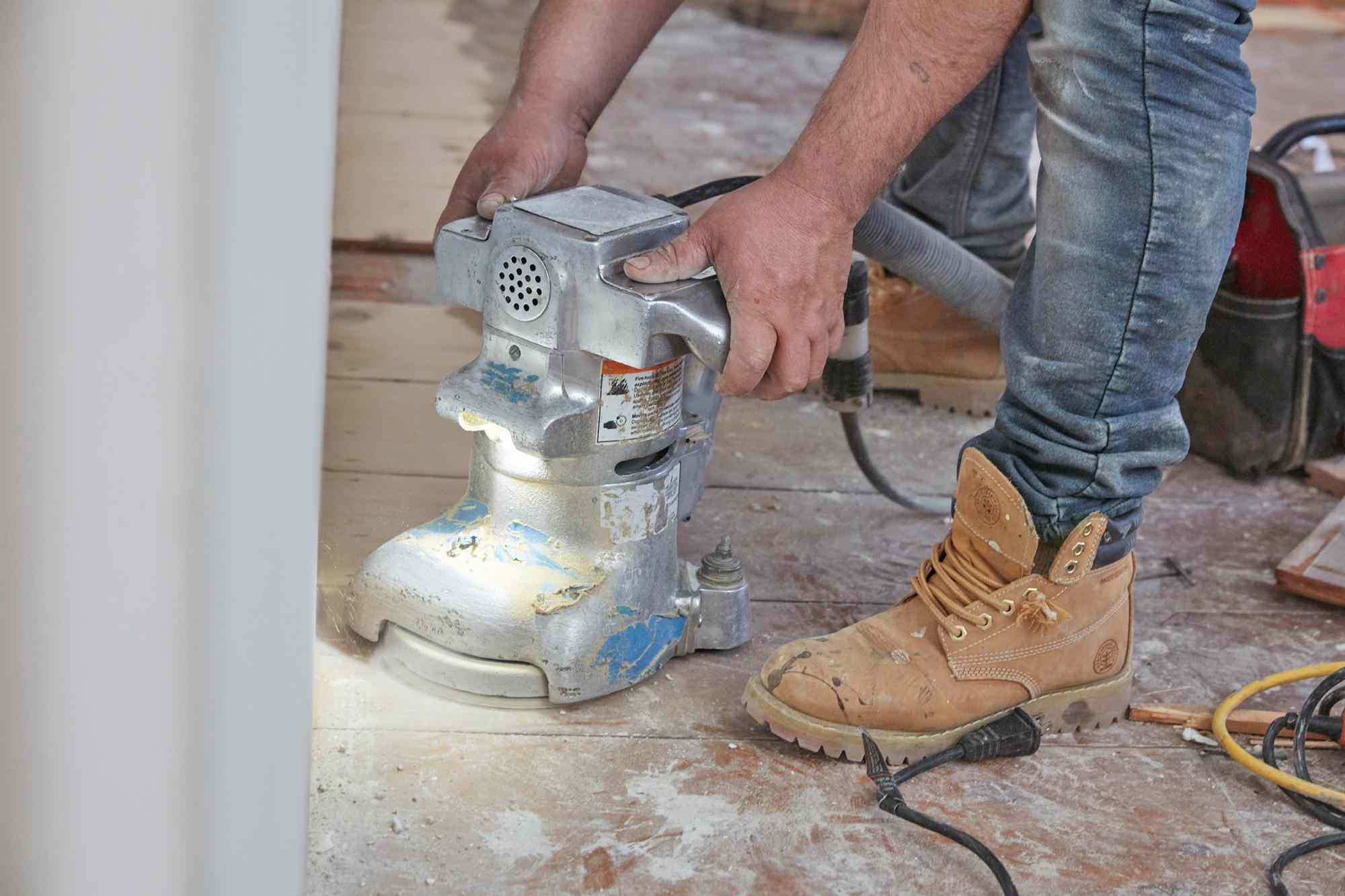 Sanding machine passing across wooden floor by hand