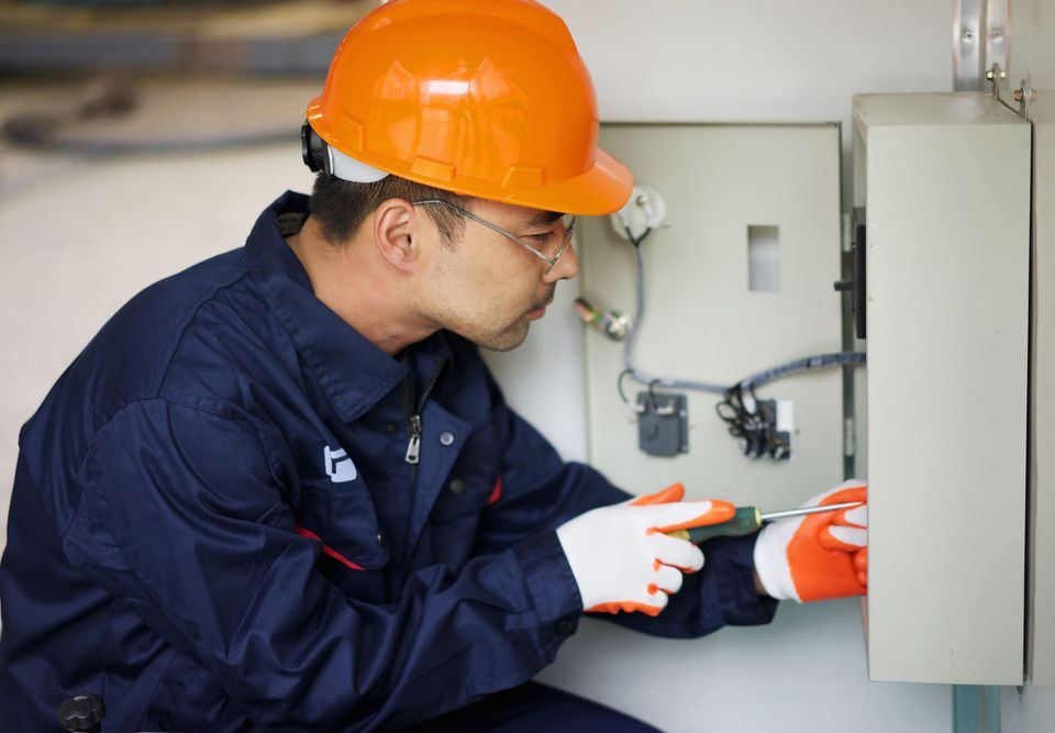 Electrician working in junction box
