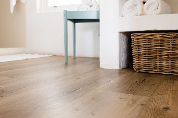 Vinyl plank flooring with wicker basket and blue side table with white rolled towels