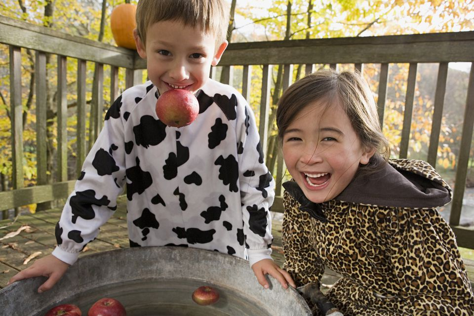 Boy and girl apple bobbing, a retro Halloween activity.